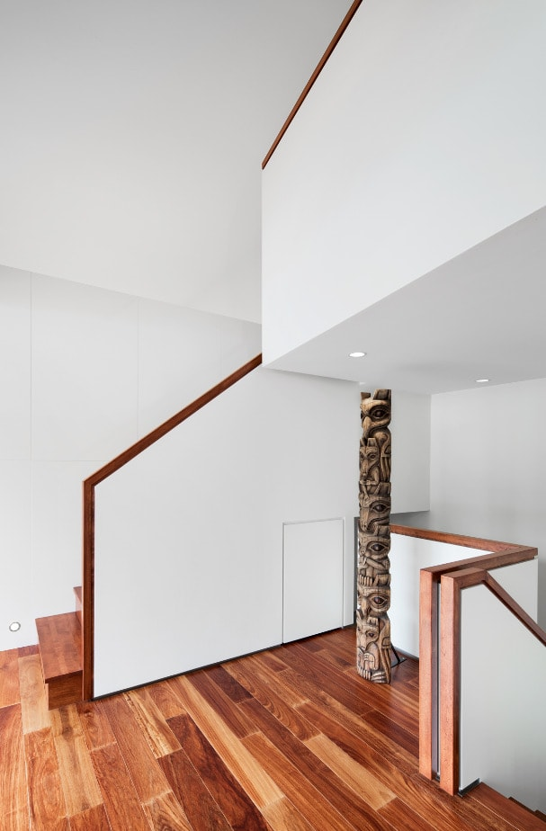 This is a close look at the landing adorned with a large wooden tiki pole that pairs well with the hardwood flooring and wooden banisters.