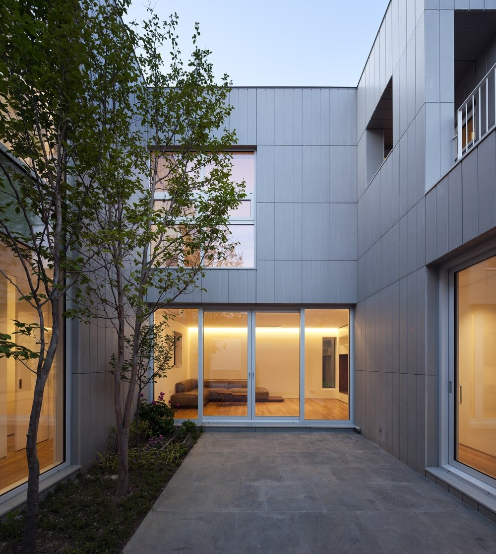 At the back of the house is a courtyard in the middle of glass walls that show the warm interiors of the house.