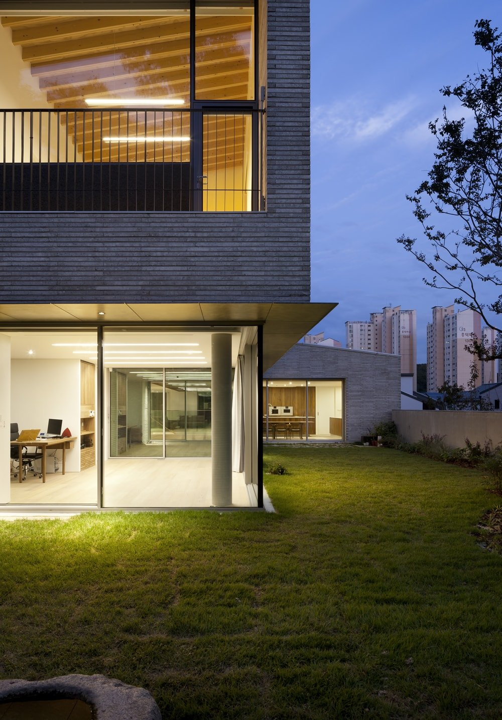 This is a nighttime view of the glass walls of the house that give glimpses of the interiors.