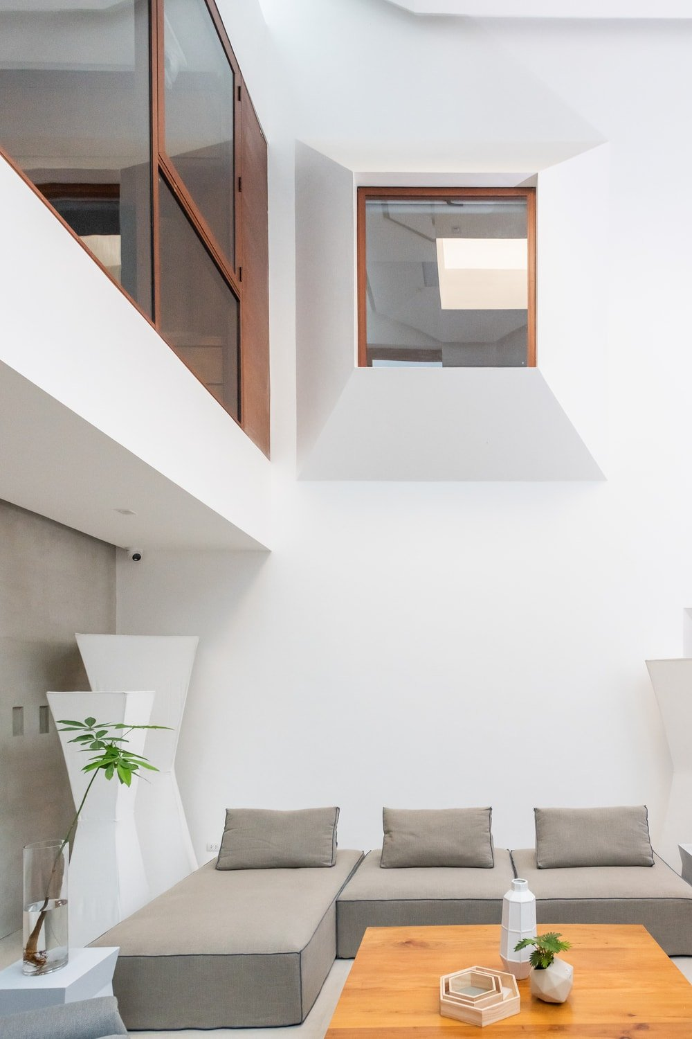 This is another look at the living room featuring the tall ceiling and indoor balcony above it with glass walls.
