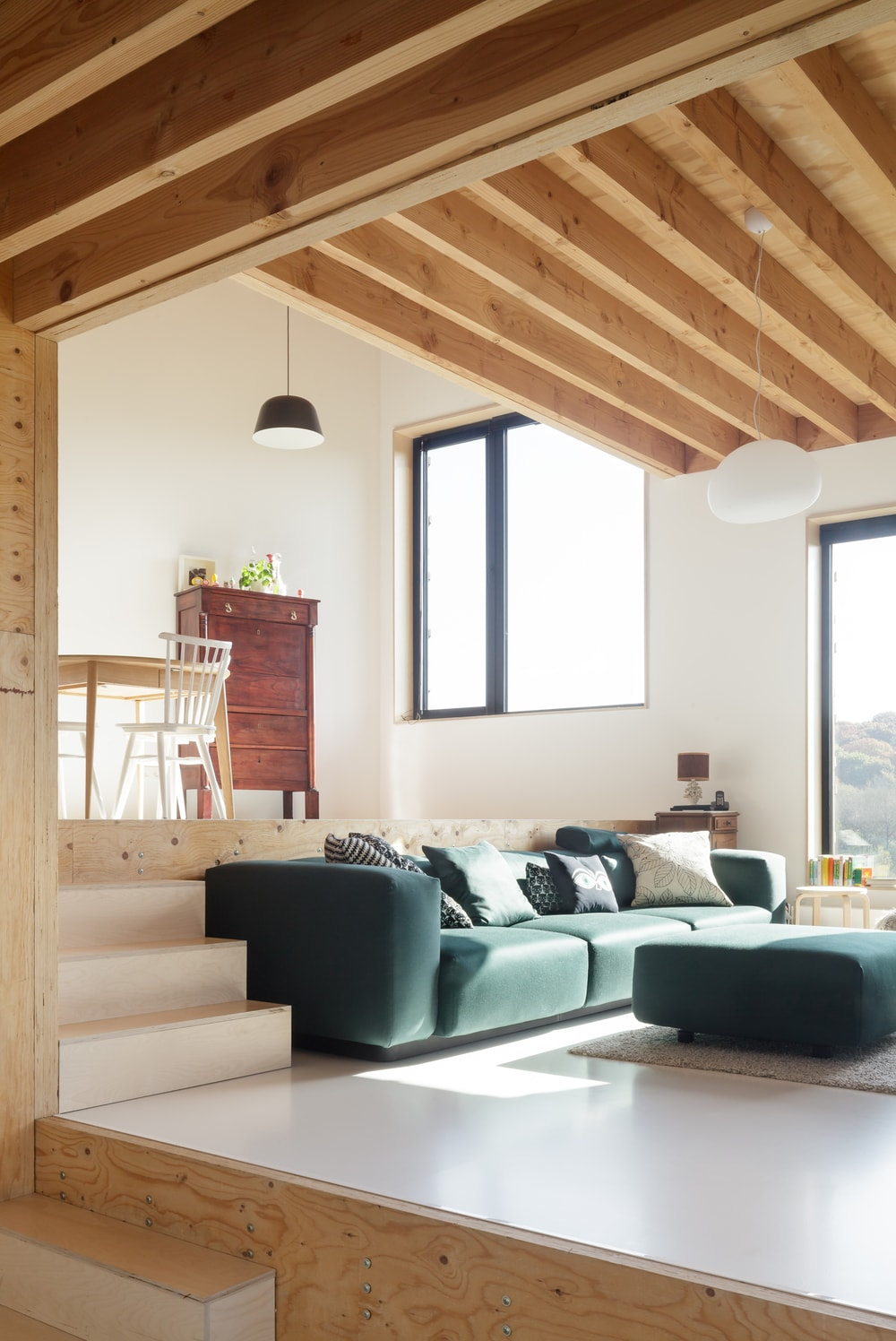 The large sectional sofa of the living room is topped with an arched and beamed wooden ceiling with a cottage-style aesthetic.