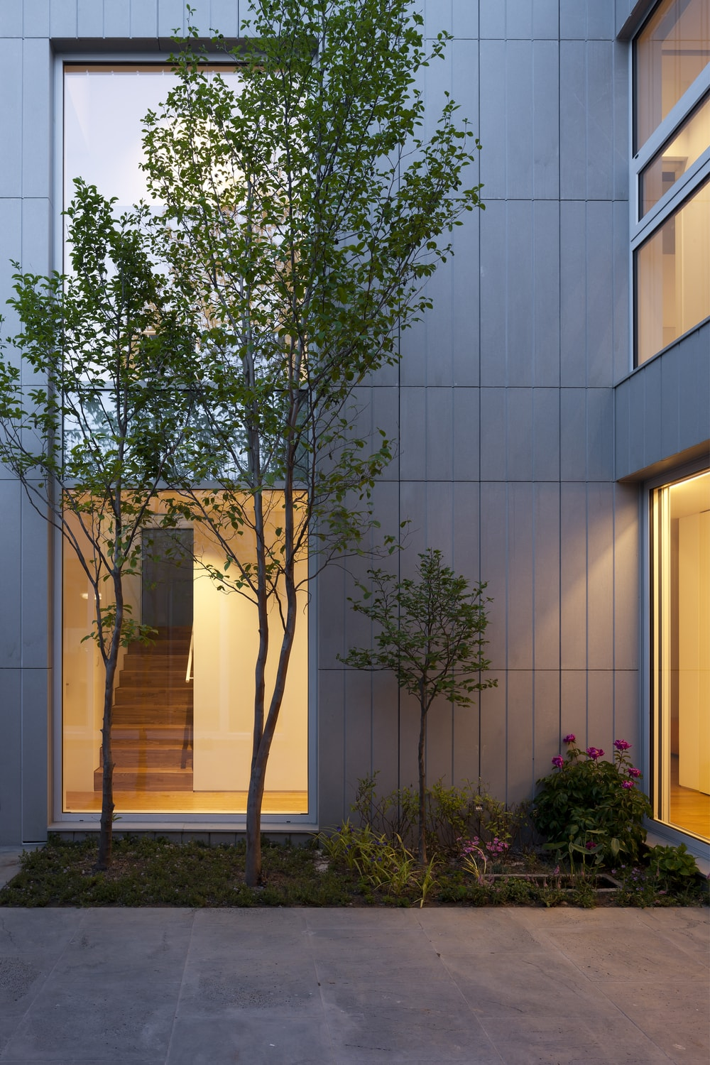 One glass wall showcases the staircase adorned with trees and flowering shrubs just outside the glass wall.