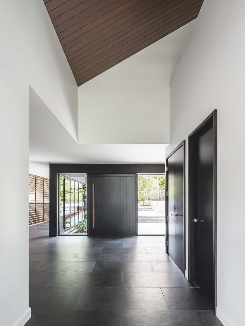 Upon entry of the house, you are welcomed by this foyer that has a large dark wooden main door and high arched ceiling.
