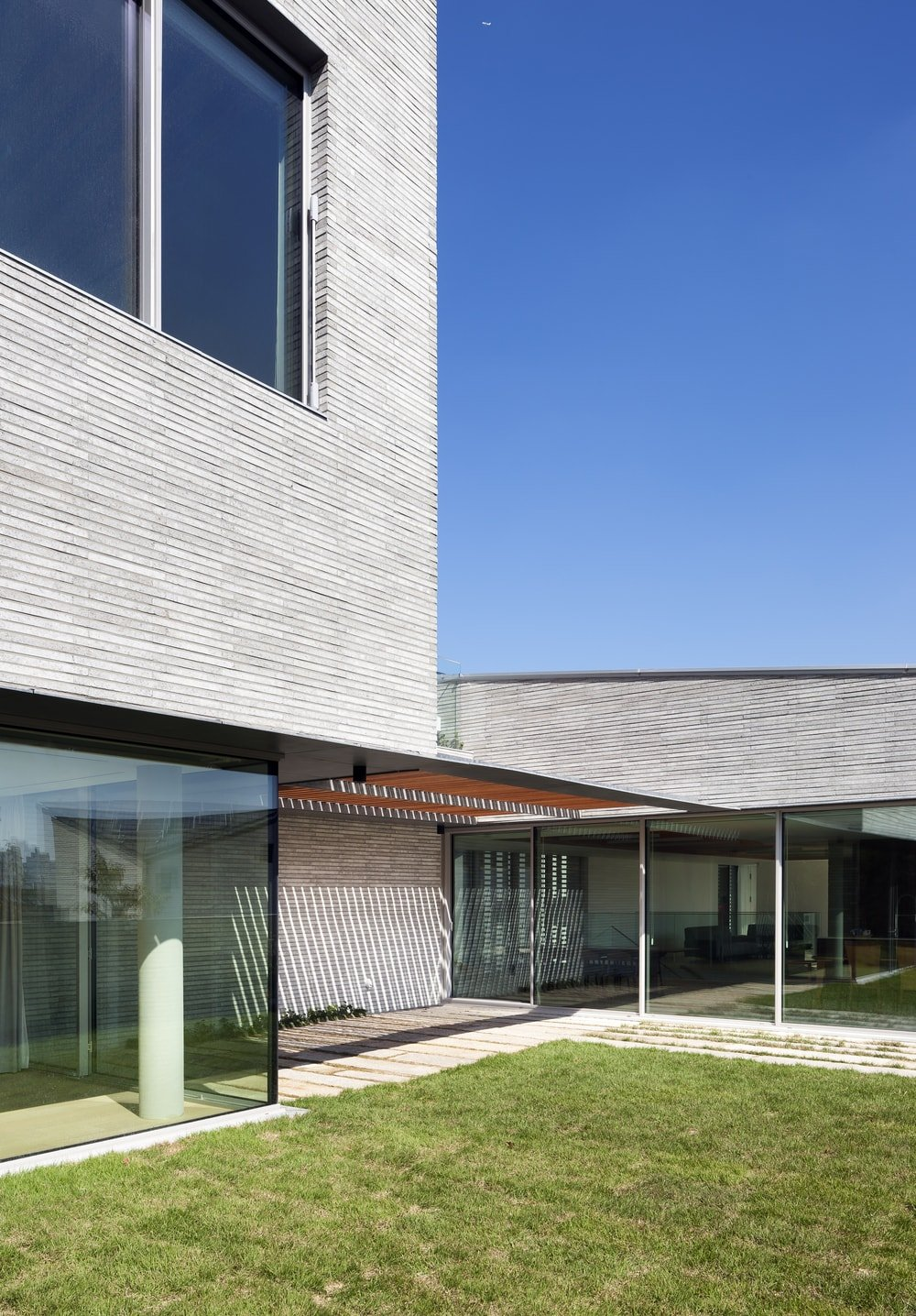 This is a side of the house with covered walkways, grass lawn and glass walls.
