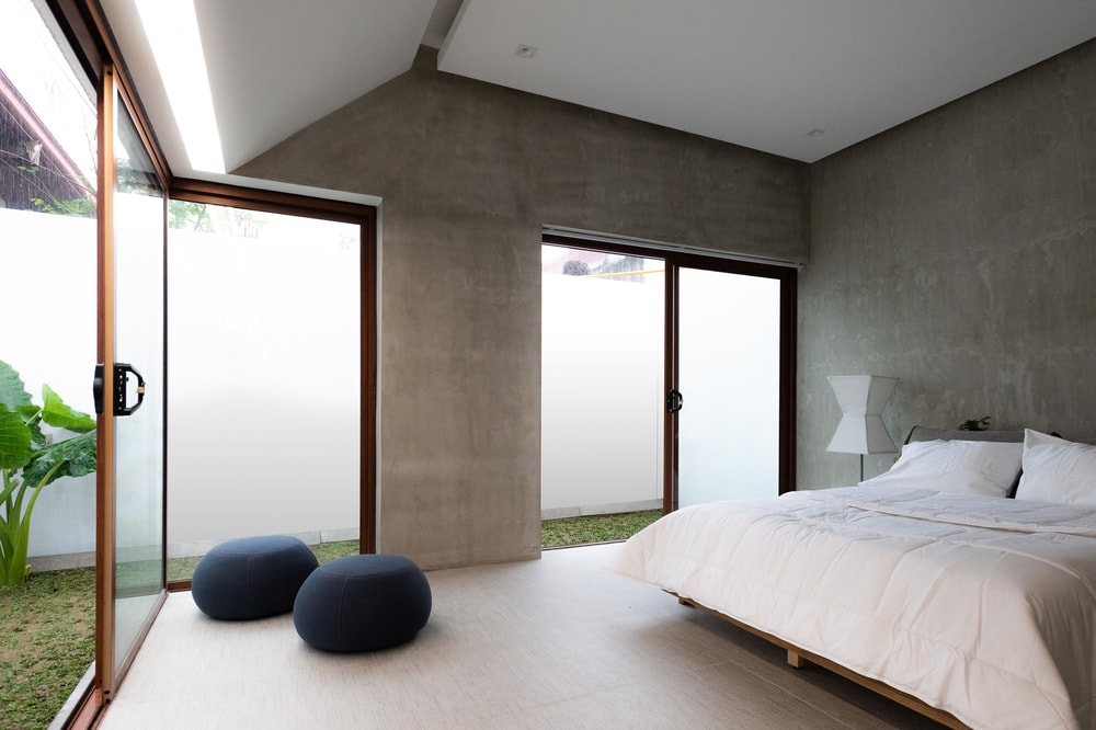 The bedroom has multiple sets of frosted glass walls that slide to serve as doors.