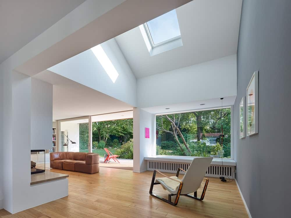 The side of the living room is topped with a tall cathedral ceiling with a couple of skylights to bring in more natural lighting that complements the bright walls.
