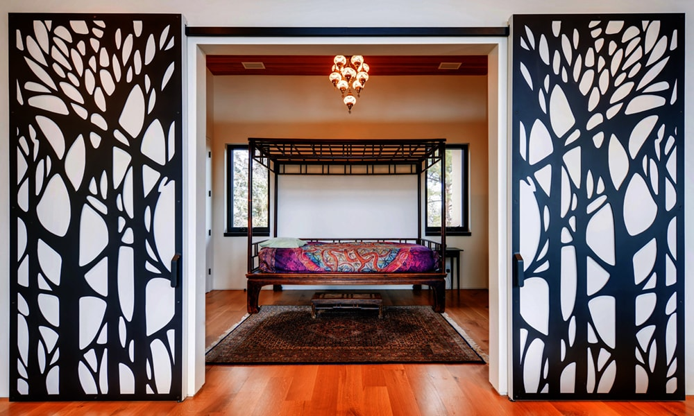 This bedroom has a large four-poster bed with its own canopy topped with a chandelier over a large patterned dark area rug.