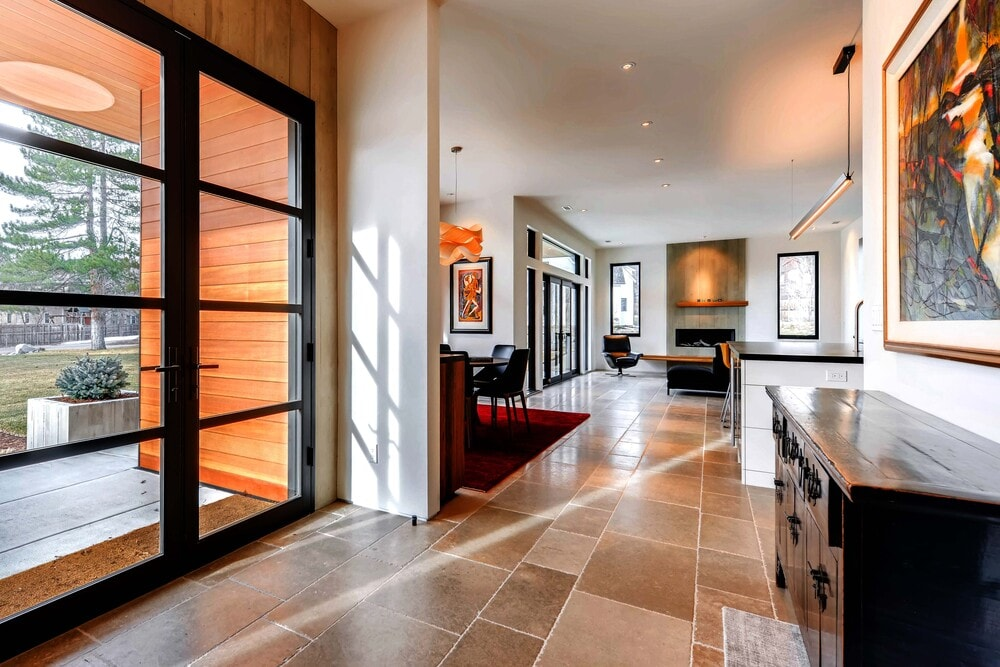 Upon entry of the house, you are welcomed by this simple foyer that has a dark waist-high cabinet topped with a colorful wall-mounted artwoork.