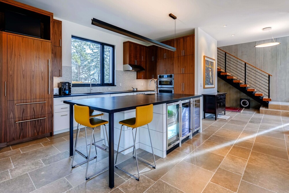 The kitchen has a large kitchen island with a dark countertop that extends to the attached table at the edge paired with modern stools.