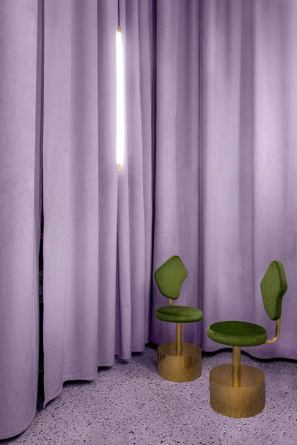 This corner of the shop has a couple of chairs that stand out against the background of purplish pink curtains.