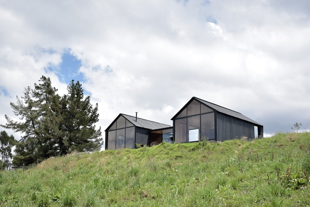 This view of the back of the house features large glass walls that span the whole side of the house facing the sweeping view.