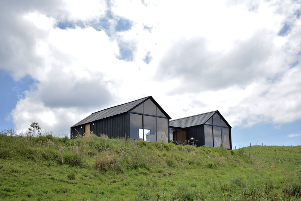 This is a view of the house that is located on top of a hill with grass and shrubs to contrast the exteriors of the house.