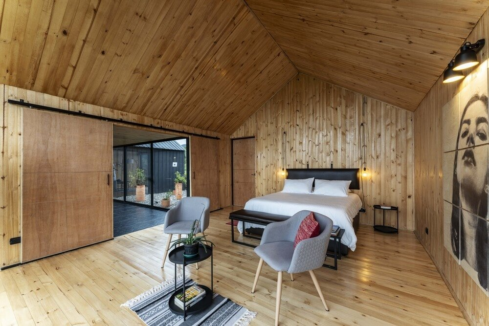 This is a full view of the bedroom with a bed that has dark cushioned frame making it stand out against the wooden shiplap walls, flooring and cathedral ceiling.