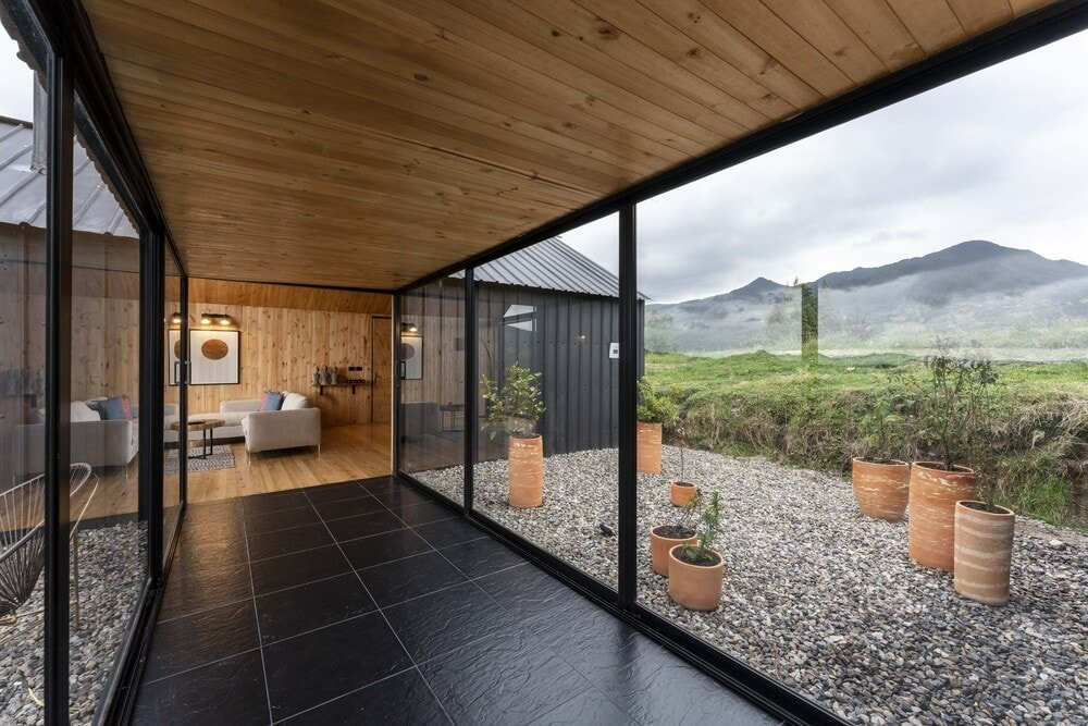 This area of the house has dark flooring tiles brightened by the glass walls flanking it.