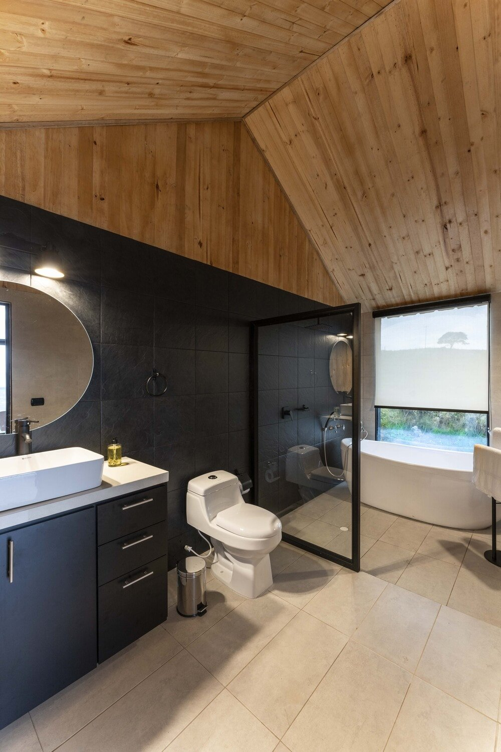 This is the bathroom with a dark wall that blends well with the cabinetry of the vanity across from the freestanding bathtub by the window.