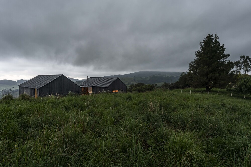 The dark tone of the exterior walls make the house stand out against the surrounding grass lands and occasional tall trees.