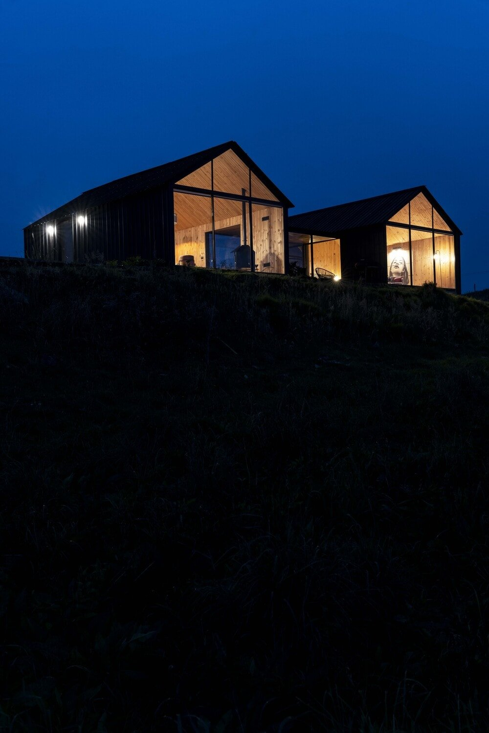 This is a nighttime view of the house that showcases the warm glow of the house.