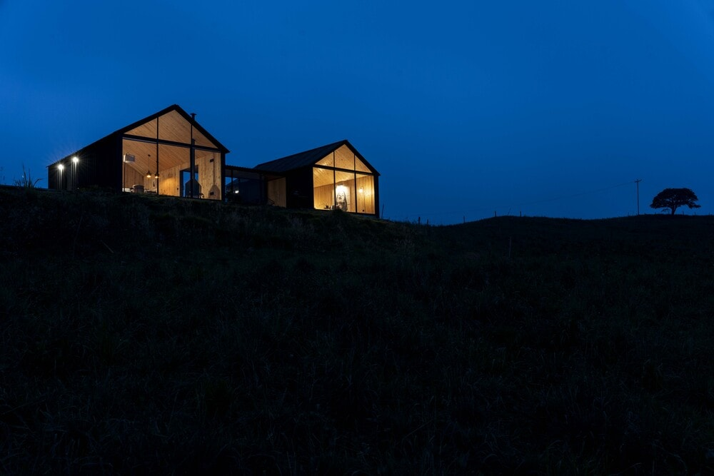 The house stands out against the surrounding dark landscape with its warm glow.