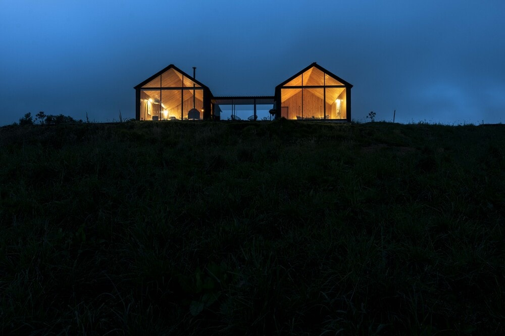 The warm glow of the interior lights of the house ezcapes through the large glass walls.