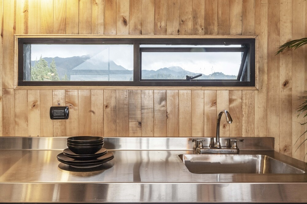 This is a close look at the stainless steel countertop and backsplash of the kitchen complemented by the wooden shiplap walls.
