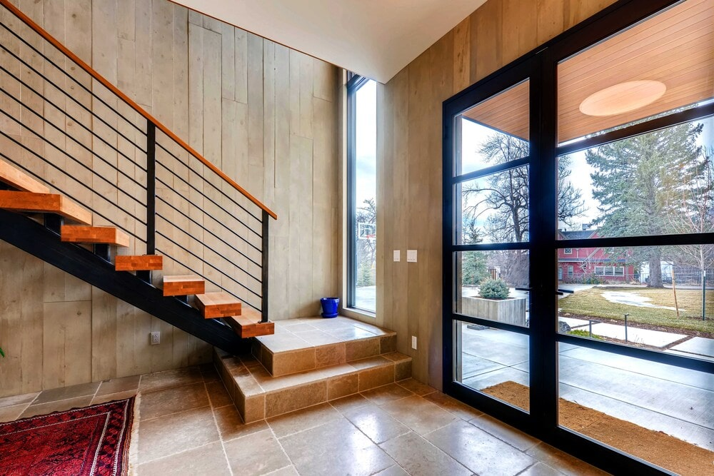 On the side of the main glass door is the staircase that has metal railings and wooden steps.