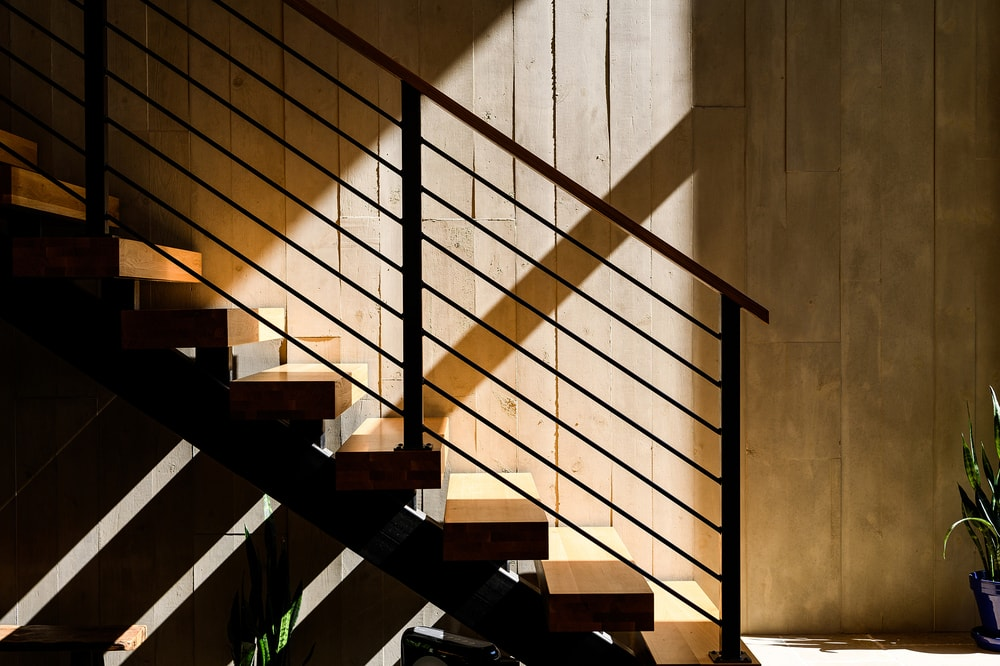 The staircase is lit by the natural lighting that comes from the glass wall on its side.