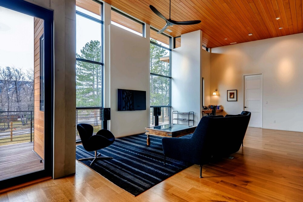This second-floor family room has a comfortable dark sofa set that stands out against the glass walls, wooden ceiling and hardwood flooring.