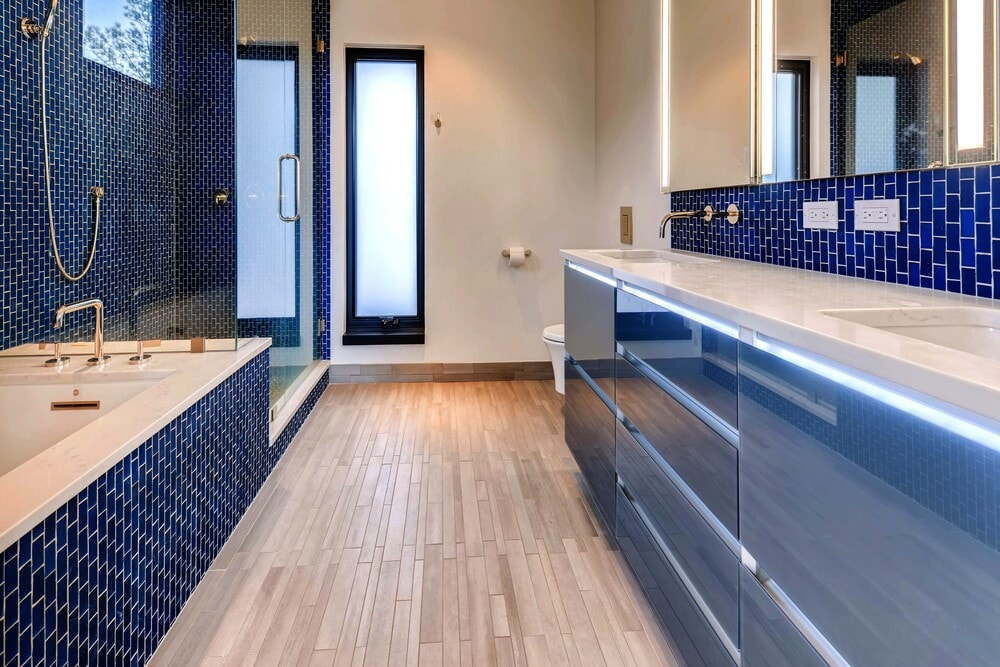 The bathroom has bright blue subway tiles on its walls that contrasts the surrounding beige walls and light flooring.
