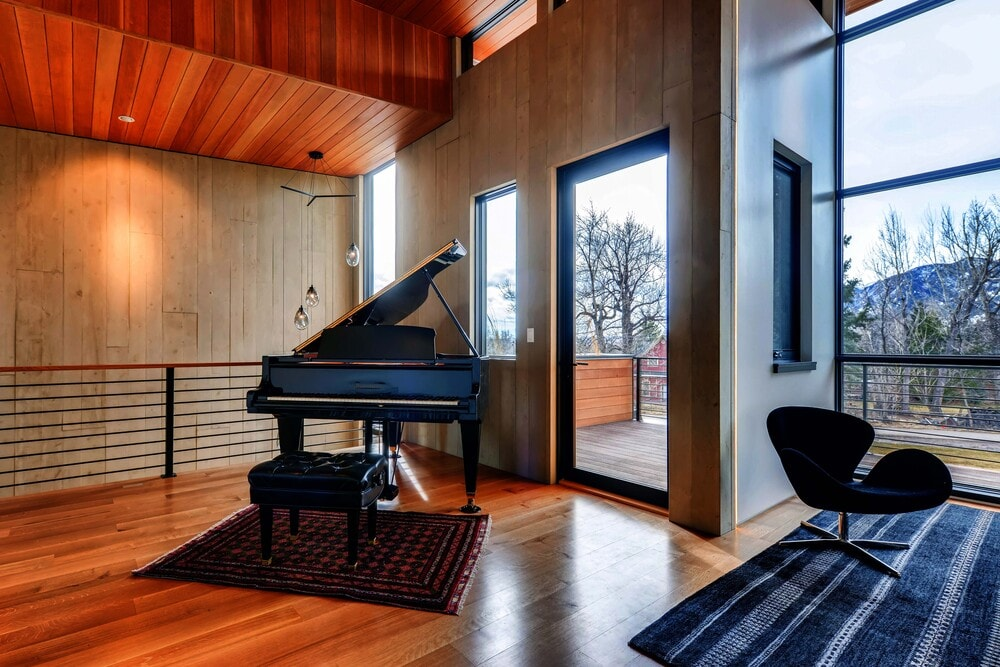 There is a grand piano at the upper level of the house near the balcony glass door.