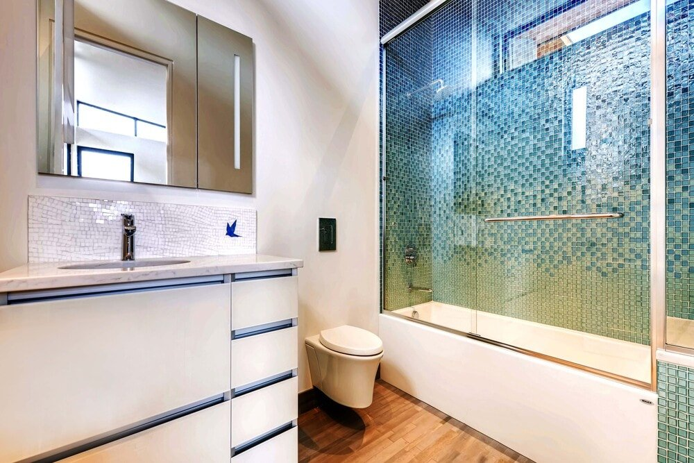 This other bathroom has a modern light-toned vanity tomatch the walls and toilet contrasted by the colorful tiles of the glass-enclosed shower area.
