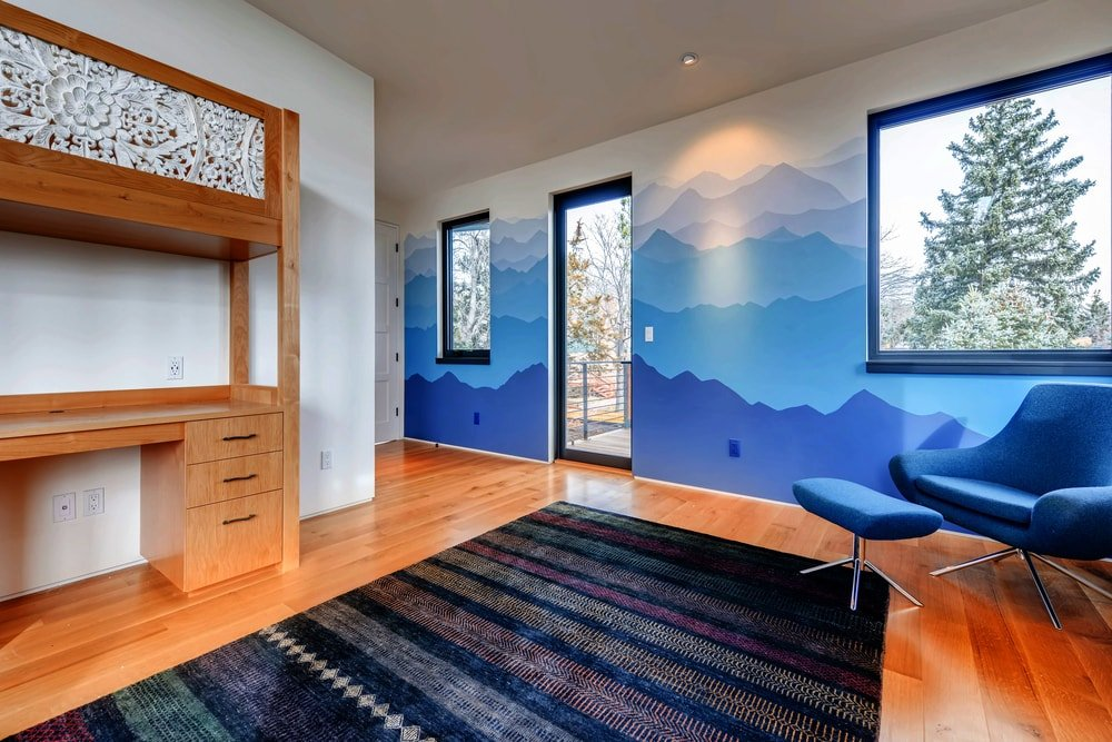 This home office has colorful walls, natural lighting and a large wooden desk with built-in cabinetry and drawers.