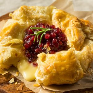 A fresh baked brie in puff pastry with berries on top.