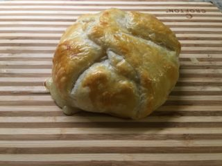 A freshly-baked piece of baked brie in puff pastry.