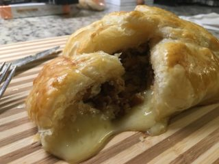 A sliced piece of baked brie in puff pastry showcasing the filling.