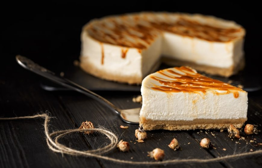 Basic cheesecake with caramel toppings on a dark surface.