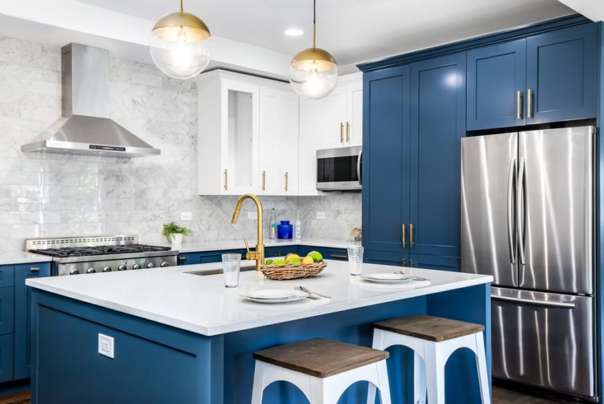 This is a close look at a kitchen island that has blue cabinetry and kitchen island that is contrasted by the white countertop and white stools that match the ceiling.