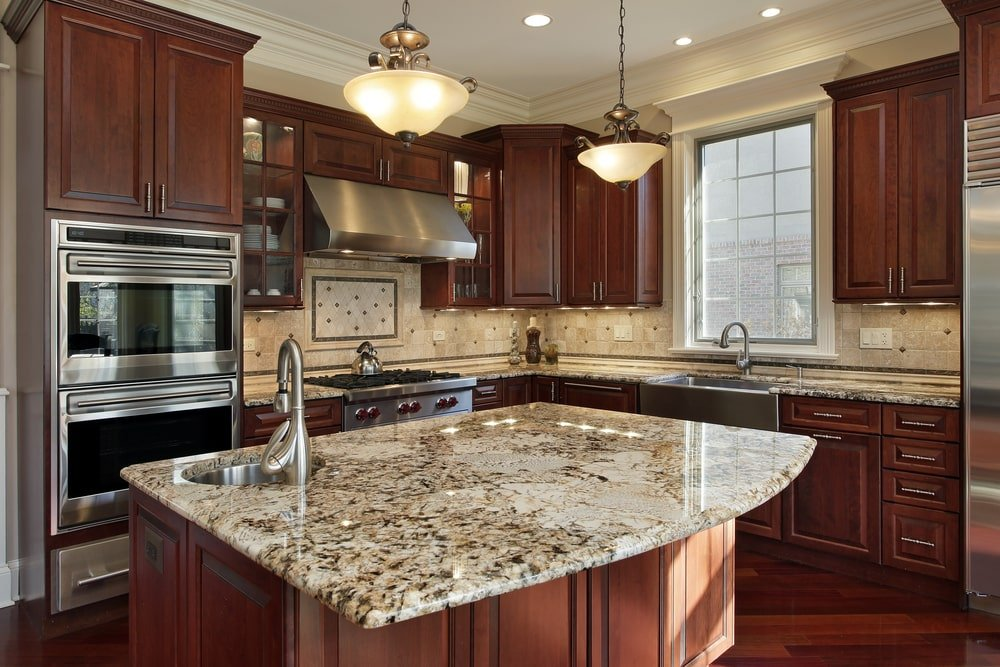 This is a close look at a kitchen island that is topped with a granite countertop that matches well with the surrounding brown wooden cabinetry of the kitchen.