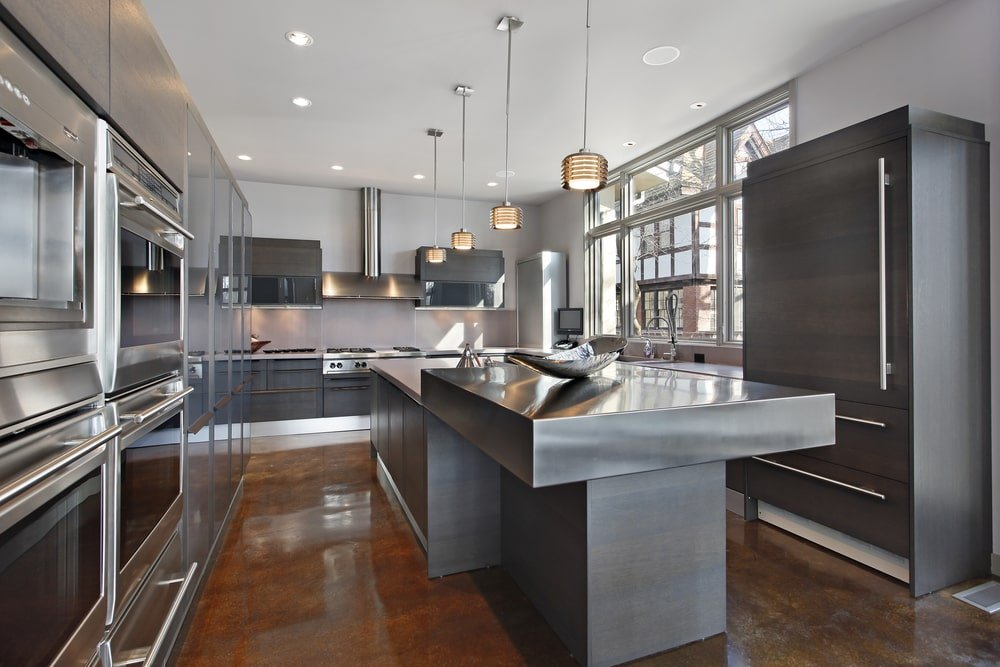 This is a close look at a kitchen that has stainless steel countertops on its kitchen island to match the gray cabinetry and stainless steel appliances.