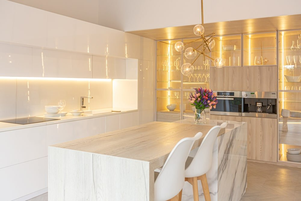 This is a bright and modern kitchen with a matching white limestone waterfall kitchen island paired with white stools.