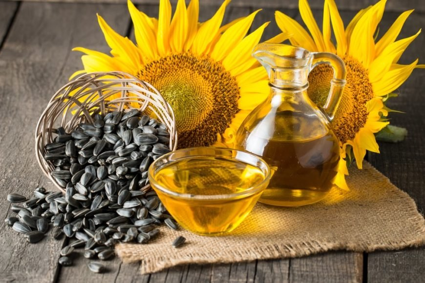 Sunflower seeds and sunflower oil adorned with sunflowers on a wooden table.