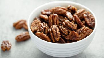 This is a bowl of candied or caramelized pecans.