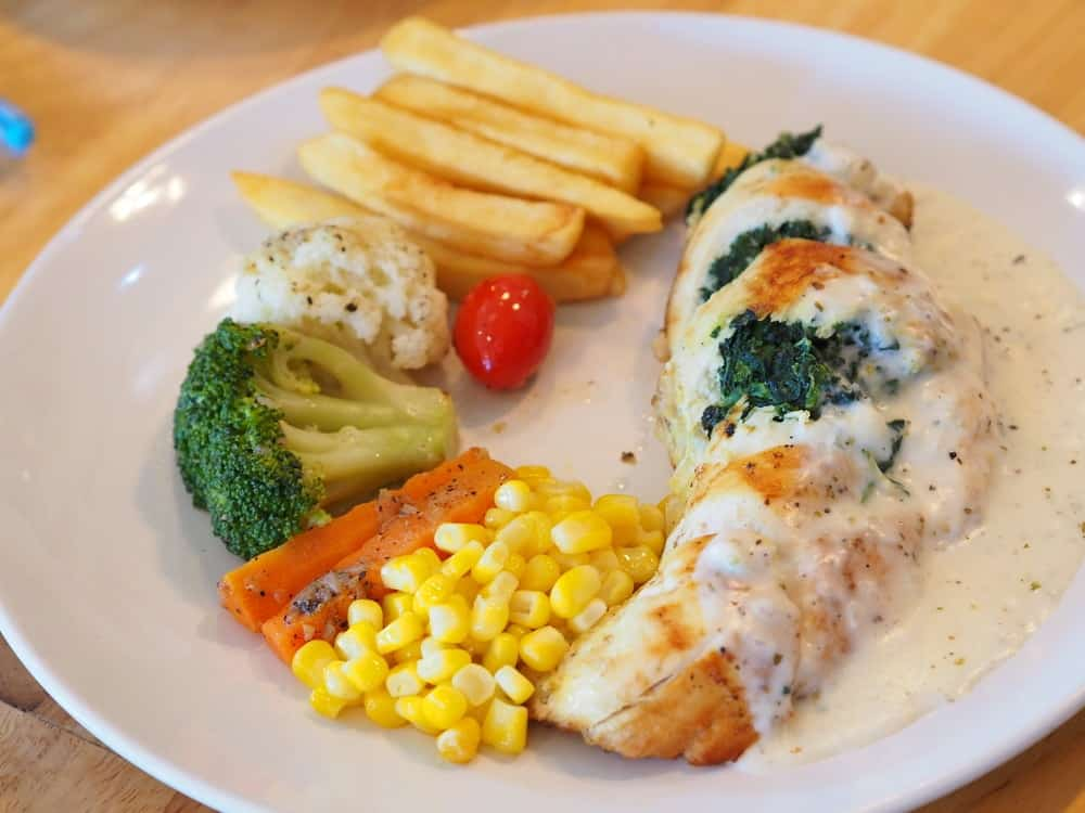 A serving of chicken cordon bleu with garnish and sides.
