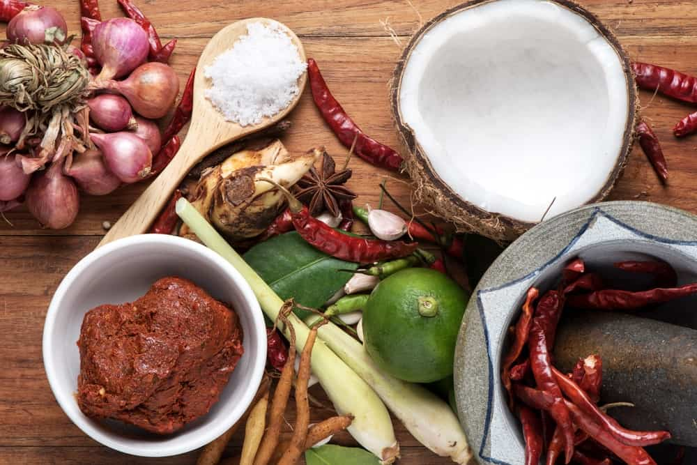 Various ingredients including fresh herbs, Asian spices, and a coconut.