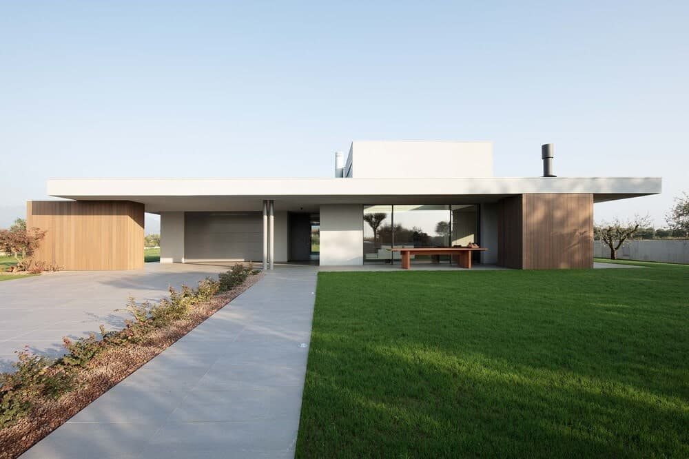 This is a front view of the house featuring a concrete driveway, walkway and a large grass lawn that complements the simple design of the house with white structures and a large glass wall.