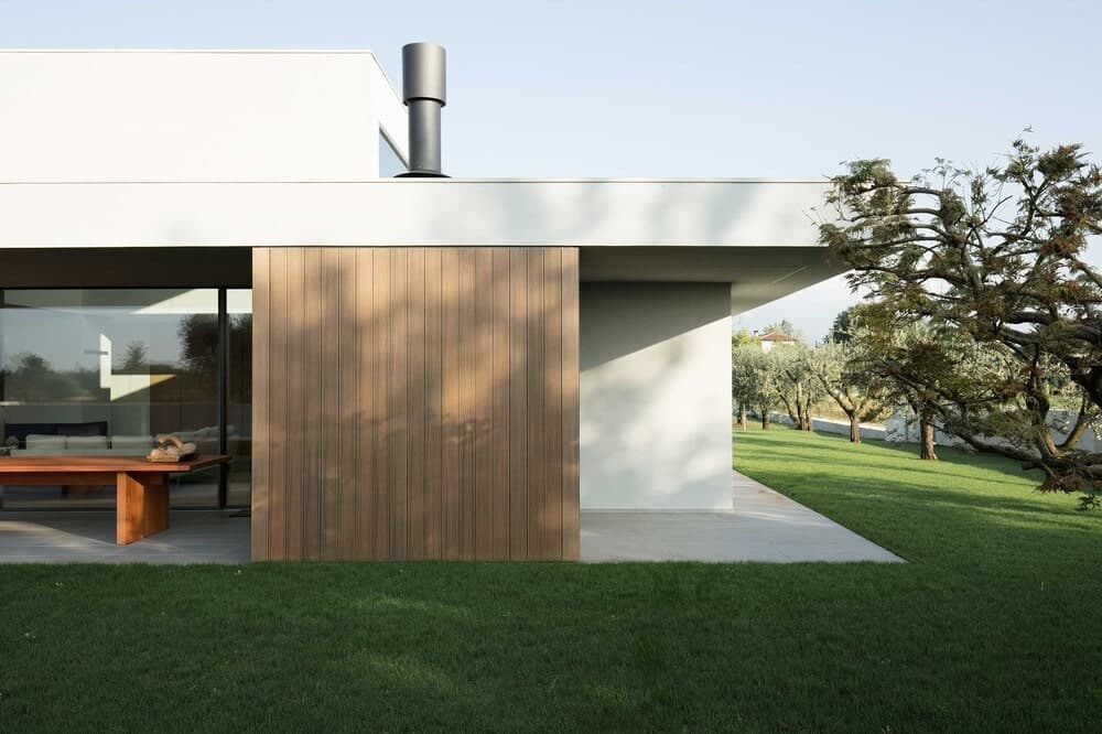This is a look at the side of the house with earthy wooden walls and green lawn for contrast.