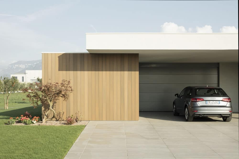 This is a close look at the car port with a large concrete driveway.