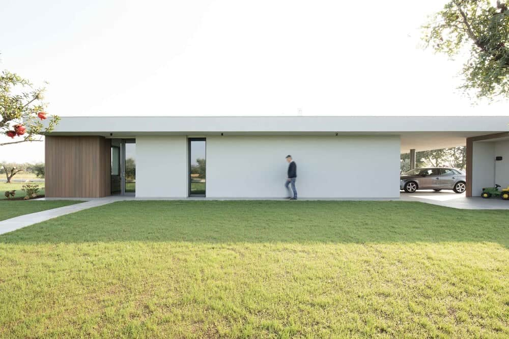 This is a view of the back of the house with a large green lawn to complement the beige wall.