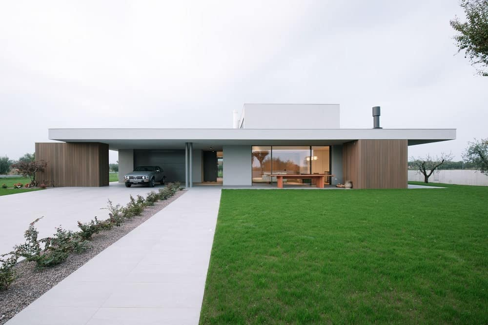 This is a front view of the exterior of the house with a large concrete driveway and walkway on the side of the green lawn.