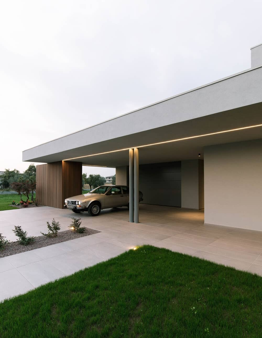 This is a close look at the main entrance of the house by the car port with a walkway by the grass lawn.