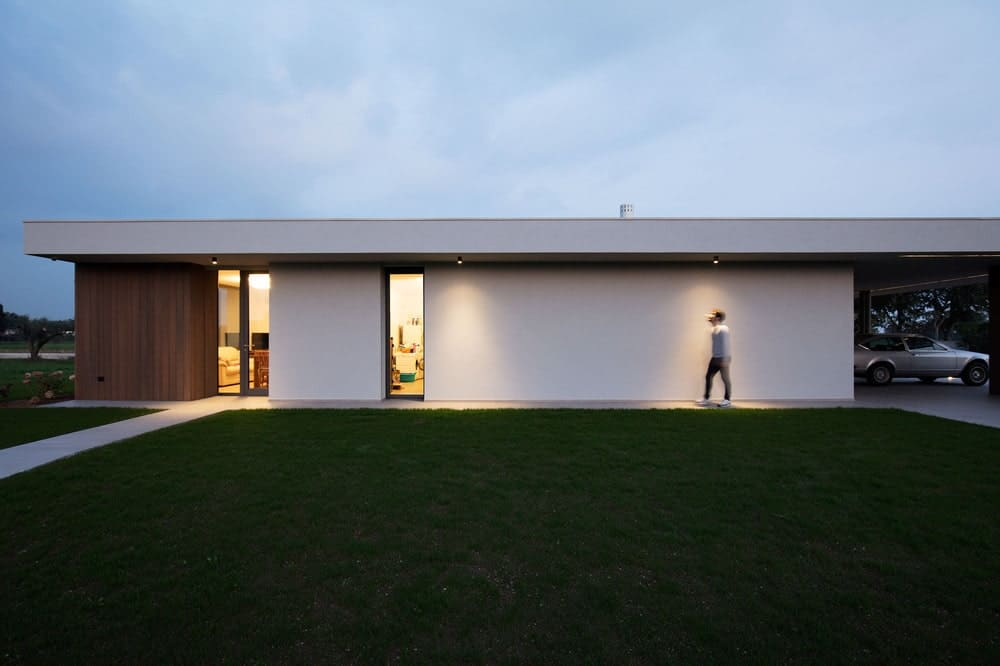 This is a nighttime view of the house exterior showcasing the exterior lights and warm glow of the window and door.